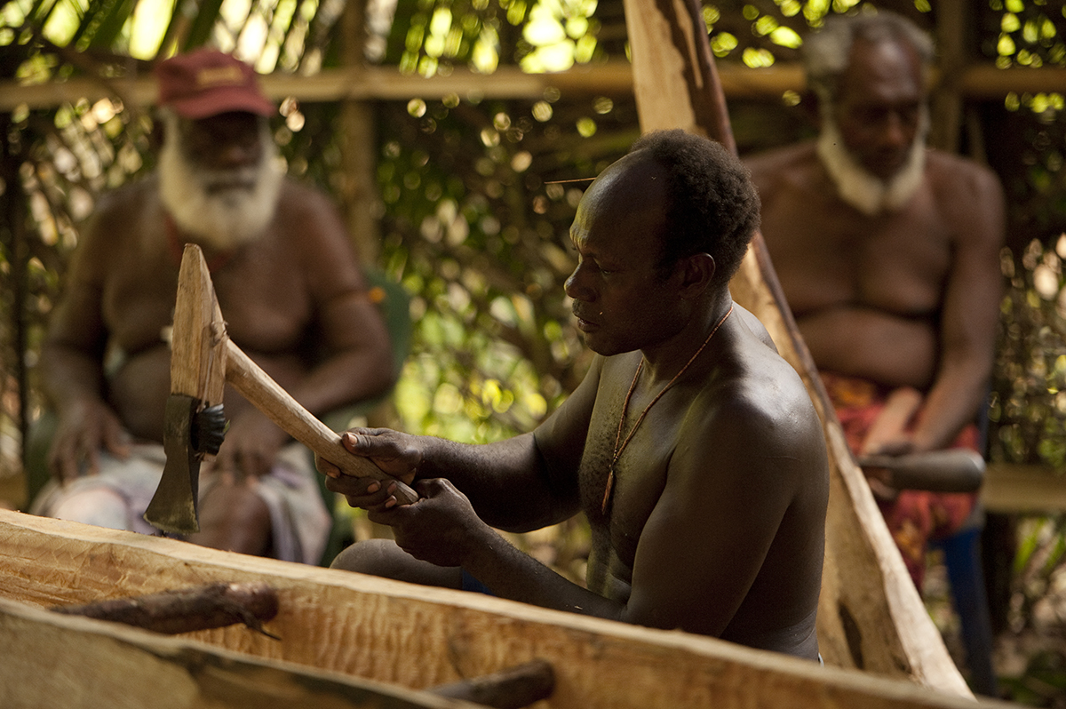 Master carver Ambrose Katlih at work on the canoe under the watchful eyes of elders, Michael Solgas and Joseph Baras.